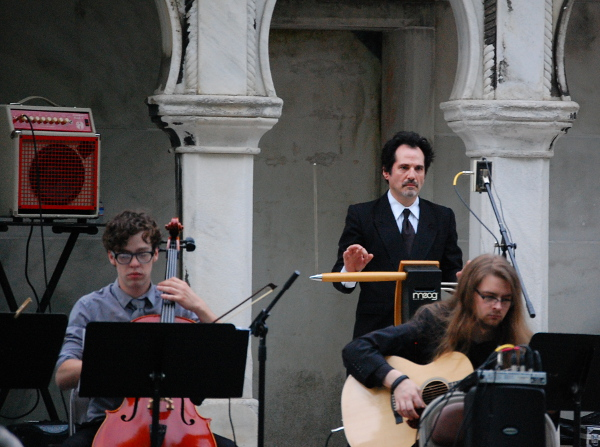 Mano Divina plays the theremin between Jonathan Salmon on cello (left) and Daniel Whitehawk on guitar (right).