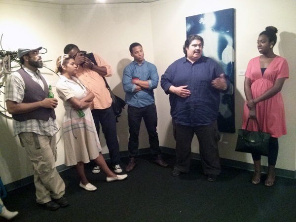 "Members of the Smoke School of Art Collective speak at the gallery talk for ""Pack a Pistol"" at the Tubman Museum"