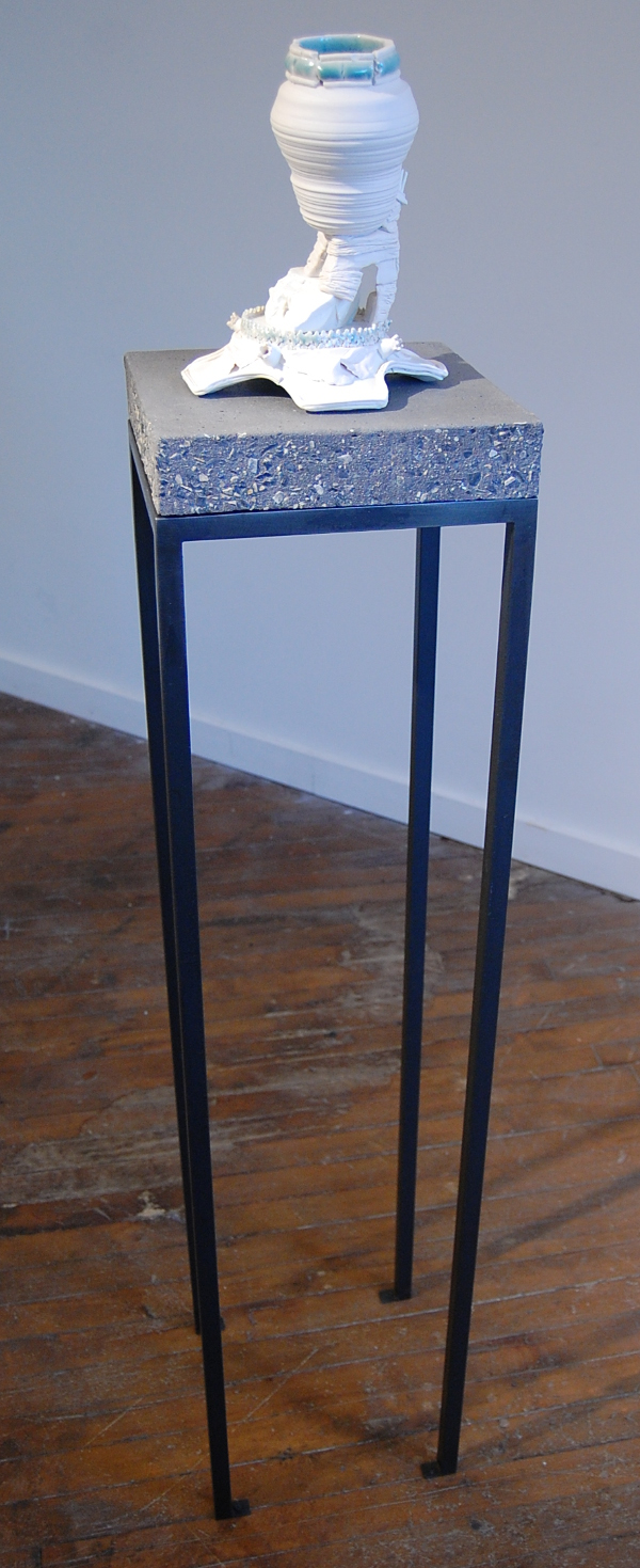 "Terri Saulin Frock, ""Perforated Stretcher Bond w/ Projecting Fins"" showing the tall steel and concrete pedestal."